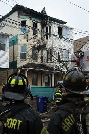 Bridgeport firefighters at the scene of a fire in a three-story house, 69 Ives Court in Bridgeport, Conn., Feb. 5th, 2013. Photo: Ned Gerard / Connecticut Post