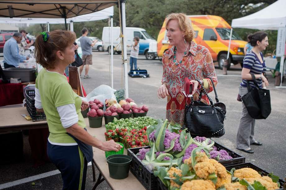 Theresa Atkinson of Atkinson Farms in Spring talks with Sherry Fox of the Westchase District. The Westchase District is planning to start its own farmers market in a few months. Photo: R. Clayton McKee, Freelance / © R. Clayton McKee