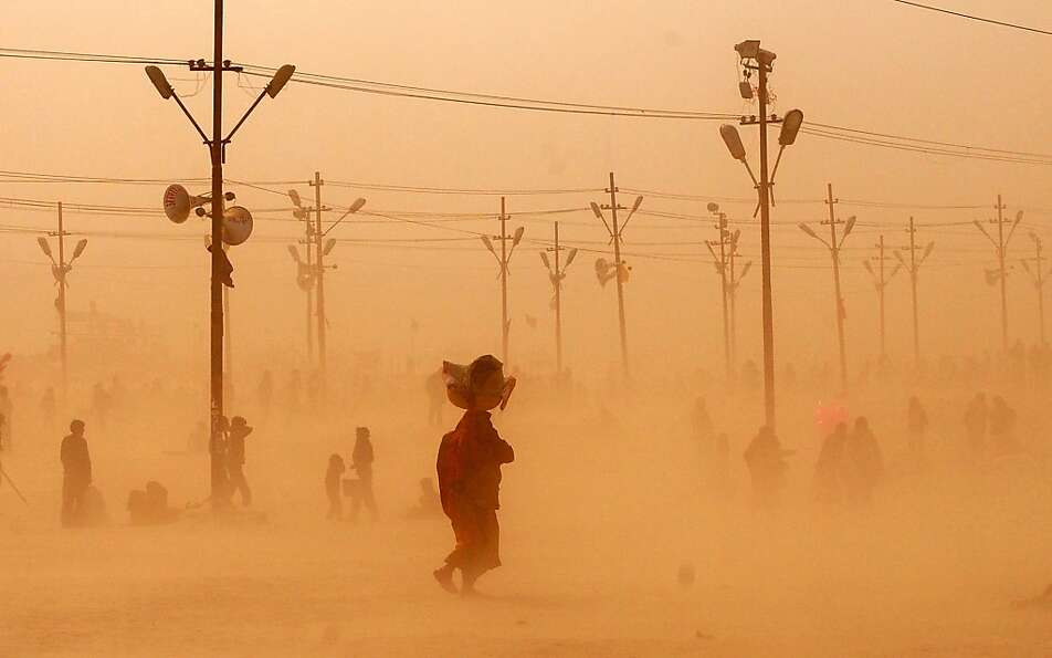 Indian Hindu devotees walk through a dust storm at the Sangam after taking a holy dip at the conflue