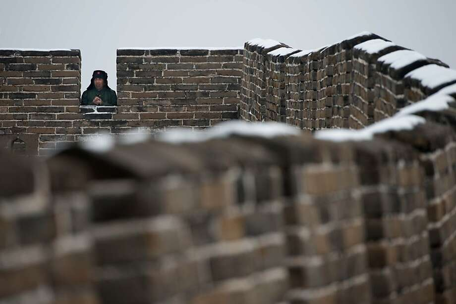 Buy my stuff or I'll jump: A vendor on the Great Wall of China in Mutianyu appears to be on the outside of the wall looking in. Photo: Ed Jones, AFP/Getty Images