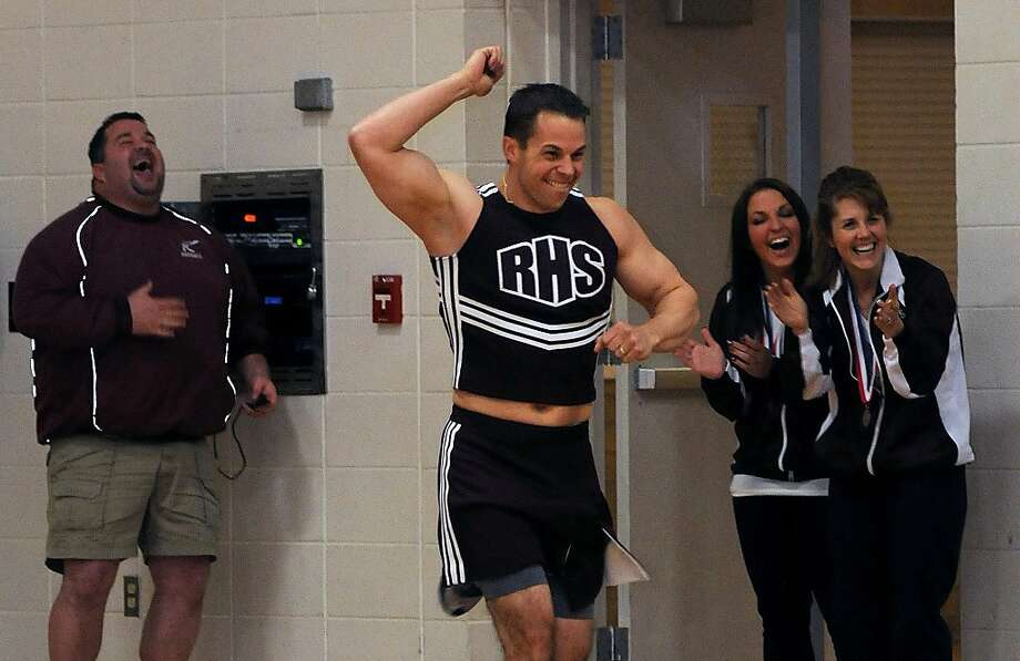 A grown man dressed as a cheerleader? Hilarious! School officials crack up as Athletic Director Scott Daly runs in a cheerleader uniform in front of the Rockridge High School student body in Edgington, Ill. Daly promised the competitive cheer team he would wear the outfit if they brought back hardware from the two-day state competition. They came in second. Photo: Todd Welvaert, Associated Press