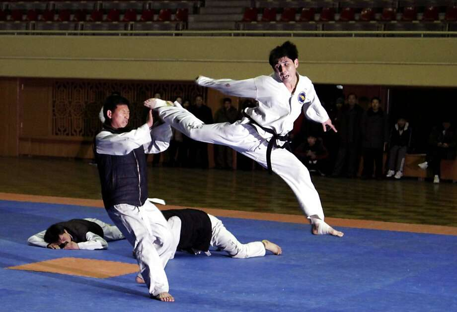 Two down, one to go: A Taekwondo competitor leaps to kick an opponent during a national sports tournament in Pyongyang. Amateur athletes from North Korea's government agencies were competing for the Paektusan Prize, which also includes basketball and volleyball matches. Photo: Jon Chol Jin, Associated Press