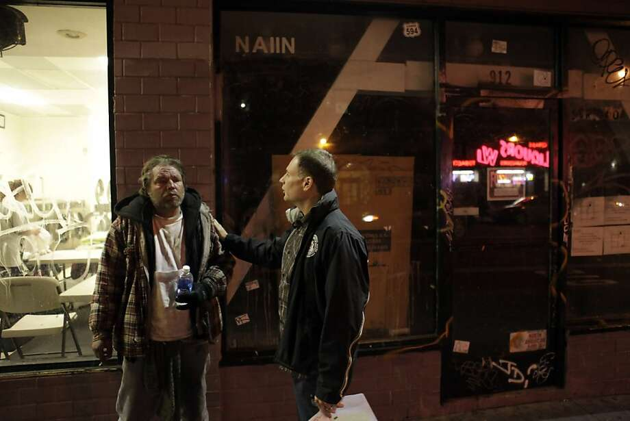 On O'Farrell Street, Dennis Broyles (left), who is homeless, talks with Dariush Kayhan, then director of homeless policy for San Francisco, about getting help through homeless services. Photo: Carlos Avila Gonzalez, The Chronicle