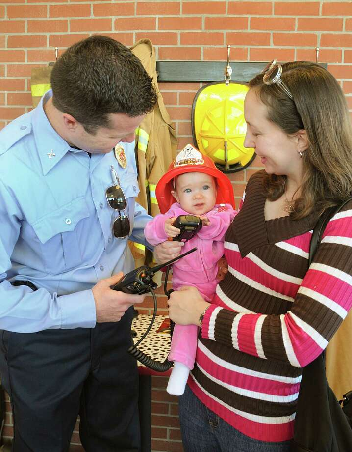 Klein FD Senior Capt. Matt Baldys shows his daughter, Kiley, and wife, Jodi, the handheld radios donated by Firehouse Subs. Photo: David Hopper, Freelance / freelance