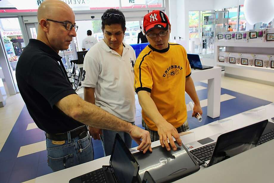 A salesman shows a Dell computer to customers at an Electric Avenue store in Miami. The Austin, Texas, company plans to move away from personal computers to focus more on higher-end data center gear. Photo: Joe Raedle, Getty Images