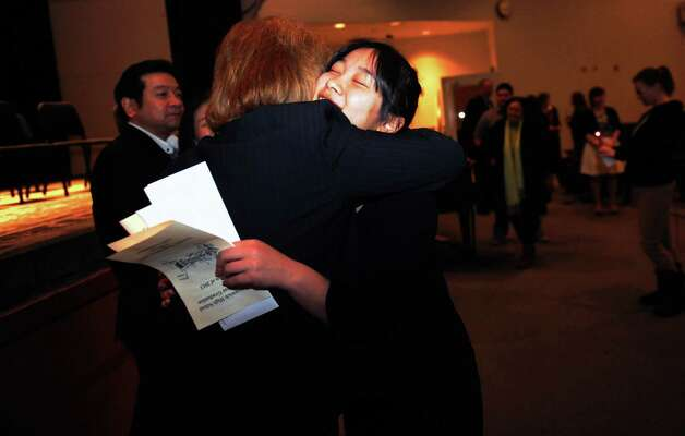 Graduate Yuriko Tashiro gets a hug from Jean DiVincenzo at the Greenwich High School's mid-year graduation in Greenwich, Conn., Tuesday, Feb. 5, 2013. Photo: Helen Neafsey / Greenwich Time