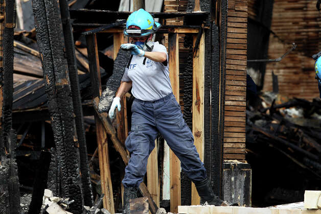 An ATF agent sifts Tuesday February 5, 2013 through the burnt remains of the Childress Memorial Church of God in Christ on North Pine. Damages to the church have been estimated at more than $3 million. The fire took place last Friday. Photo: JOHN DAVENPORT, San Antonio Express-News / ©San Antonio Express-News/Photo Can Be Sold to the Public