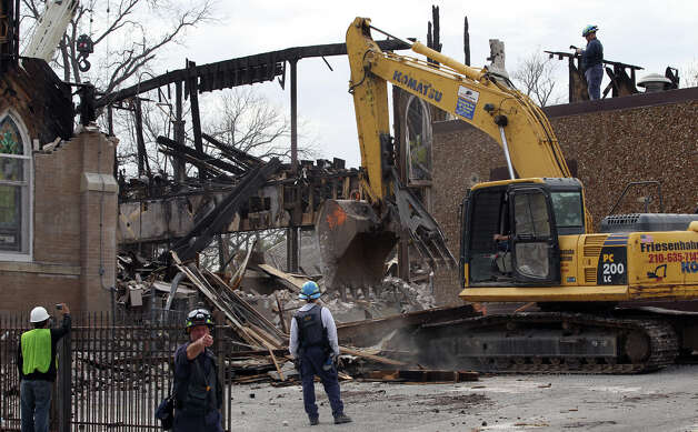 Demolition of a wall takes place Tuesday February 5, 2013 at the remains of the Childress Memorial Church of God in Christ at 901 N. Pine. The church burned down last Friday and the cause of the blaze is being investigated. Photo: JOHN DAVENPORT, San Antonio Express-News / ©San Antonio Express-News/Photo Can Be Sold to the Public