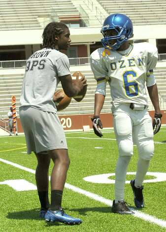 "Ozen player Tony Brown, left, who spent the game on the sidelines, talks with a teammate during first quarter action. Ozen High School held their blue and gold spring football game Friday May 18, 2012, at the Carrol A ""Butch"" Thomas Educational Support Center.  Dave Ryan/The Enterprise Photo: Dave Ryan"