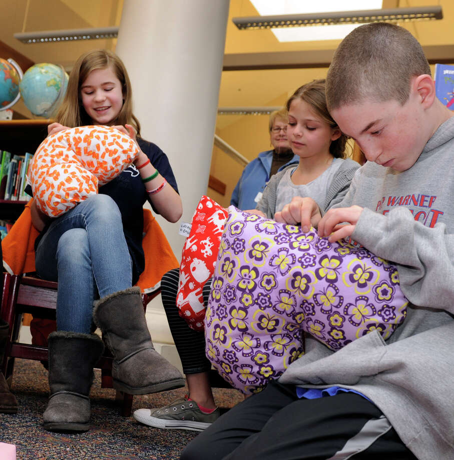 "From left, Amelia Moschitta, Ryan Berlinger and Will Enright, all 11-year-old sixth-graders, do the final sewing on pillows that will be given to young cancer patients at Columbia Prebyterian Hospital in New York. This is the second annual  ""Matthew's Hearts of Hope 'Hug a Heart' Pillow Project"" at the Sherman School, and the goal is 300 pillows. The project was started by Marie Hatcher, whose son Matthew was born with a congenital heart defect. Photo: Carol Kaliff / The News-Times"
