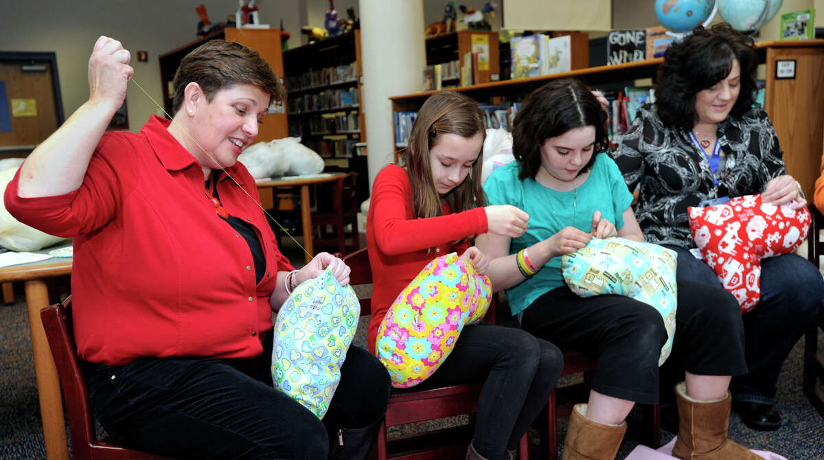 From left, Marie Hatcher; Leah Grill, 12, Emma Greene, 12; and Sue Peet, a preschool paraprofessional, sew closed pillows that they are making for Matthew's Hearts of Hope
