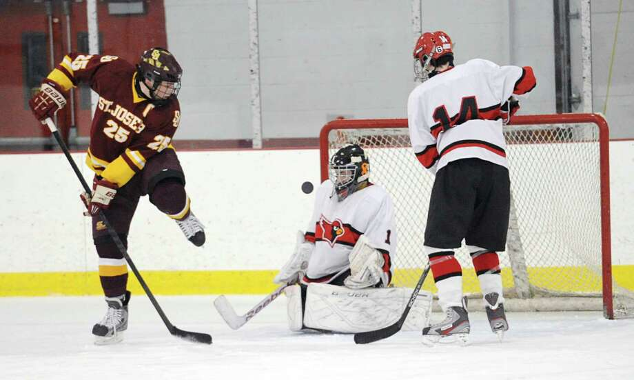 At left, Andrew Gore # 25 of St. Joseph deflects a teammate's shot past goalie Bryan Archino of Greenwich for a goal during the second period of the high school ice hockey game between St. Joseph High School and Greenwich High School at Hamill Rink in Byram, Tuesday night, Feb. 5, 2013. At right Jack Corrigan # 14 of Greenwich looks on. St. Joseph defeated Greenwich, 5-2. Photo: Bob Luckey / Greenwich Time