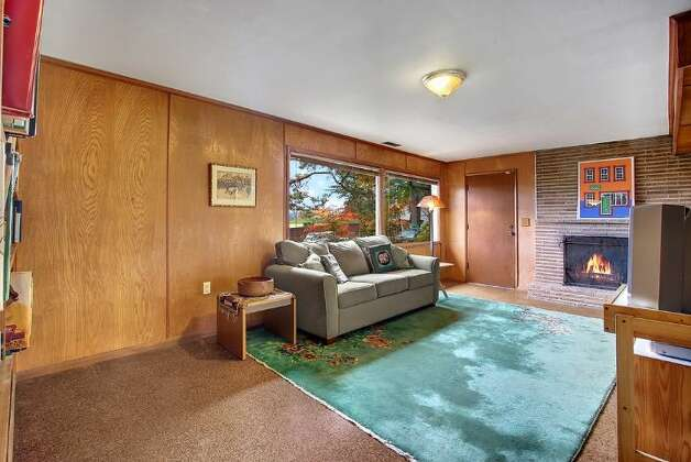 Family room of 5417 S. Orcas St. The 2,820-square-foot home, built in 1955, has three bedrooms, 2.5 bathrooms, vaulted, cedar-lined ceilings, a wine cellar, a deck, a view of Lake Washington and a two-car garage on a 9,000-square-foot lot. It's listed for $521,550. Photo: Courtesy Al Johnson/ Windermere Real Estate