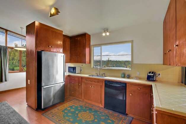 Kitchen of 5417 S. Orcas St. The 2,820-square-foot home, built in 1955, has three bedrooms, 2.5 bathrooms, vaulted, cedar-lined ceilings, a family room with a fireplace, a wine cellar, a deck, a view of Lake Washington and a two-car garage on a 9,000-square-foot lot. It's listed for $521,550. Photo: Courtesy Al Johnson/ Windermere Real Estate