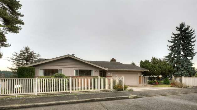 Front of 5724 55th Ave. S. The 2,880-square-foot house, built in 1955, has three bedrooms, 1.75 bathrooms, a recreation room with a fireplace and bar, a shop, a deck and views of Lake Washington on an 8,184-square-foot lot. It's listed for $524,888. Photo: Courtesy Rhonda Smith/Windermere Real Estate