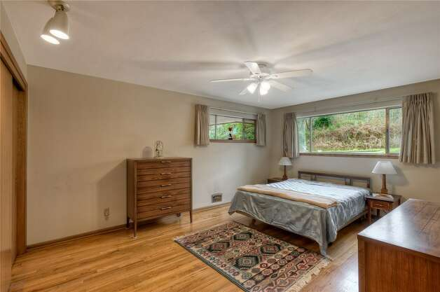 Bedroom of 5724 55th Ave. S. The 2,880-square-foot house, built in 1955, has three bedrooms, 1.75 bathrooms, a recreation room with a fireplace and bar, a shop, a deck and views of Lake Washington on an 8,184-square-foot lot. It's listed for $524,888. Photo: Courtesy Rhonda Smith/Windermere Real Estate