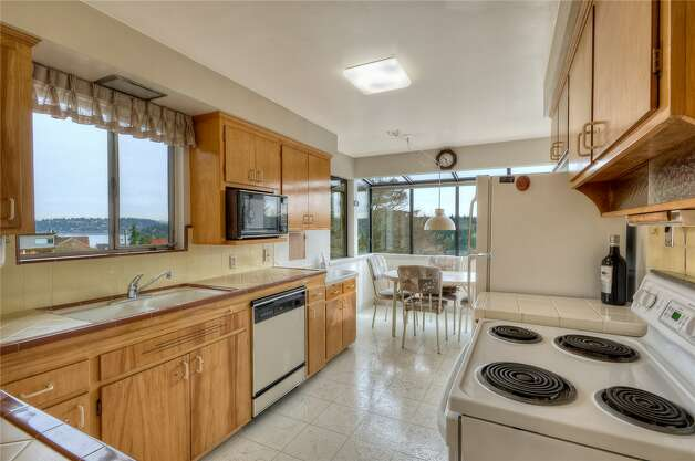 Kitchen of 5724 55th Ave. S. The 2,880-square-foot house, built in 1955, has three bedrooms, 1.75 bathrooms, a recreation room with a fireplace and bar, a shop, a deck and views of Lake Washington on an 8,184-square-foot lot. It's listed for $524,888. Photo: Courtesy Rhonda Smith/Windermere Real Estate