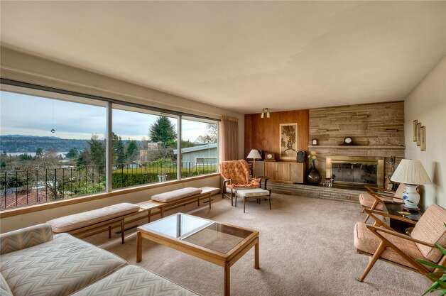 Living room of 5724 55th Ave. S. The 2,880-square-foot house, built in 1955, has three bedrooms, 1.75 bathrooms, a recreation room with a fireplace and bar, a shop, a deck and views of Lake Washington on an 8,184-square-foot lot. It's listed for $524,888. Photo: Courtesy Rhonda Smith/Windermere Real Estate