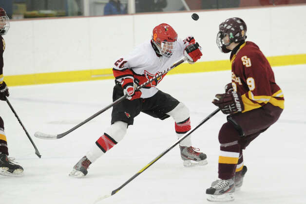 At left, Andrew Mitchell # 20 of Greenwich goes for a high puck against C.K. Keator # 9 of St. Joseph's during the boys high school ice hockey game between St. Joseph High School and Greenwich High School at Hamill Rink in Byram, Tuesday night, Feb. 5, 2013. St. Joseph defeated Greenwich, 5-2. Photo: Bob Luckey / Greenwich Time