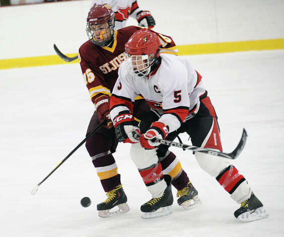 At left, Ryan Corcoran # 15 of St. Joseph's fights William Waesche # 5 of Greenwich for the puck during the boys high school ice hockey game between St. Joseph High School and Greenwich High School at Hamill Rink in Byram, Tuesday night, Feb. 5, 2013. St. Joseph defeated Greenwich, 5-2. Photo: Bob Luckey / Greenwich Time