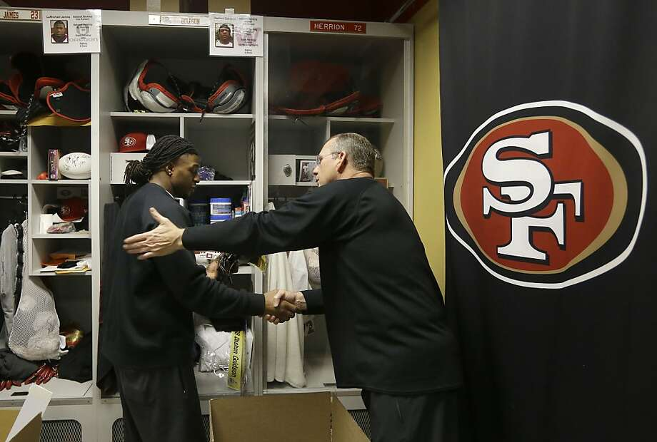 Dashon Goldson shakes hands with a 49ers staff member after cleaning out his locker at the team's Santa Clara facility. Photo: Jeff Chiu, Associated Press