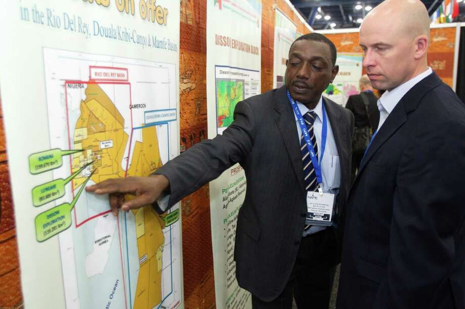 Jifon Francis, left, of the National Hydrocarbons Corporation of Camerooon, shows leasing blocks in Cameroon to Jonas Harrell, of Noble Energy, during the NAPE Expo at the George R. Brown Convention Center Tuesday, Feb. 5, 2013, in Houston. Photo: Brett Coomer, Houston Chronicle / © 2013 Houston Chronicle
