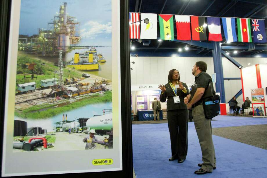 Sharon Kuhn, exploration geologist for Staatsolie, talks about oil lease blocks in Suriname with Sean Lewis, of ExxonMobile, during the NAPE Expo at the George R. Brown Convention Center Tuesday, Feb. 5, 2013, in Houston. Photo: Brett Coomer, Houston Chronicle / © 2013 Houston Chronicle