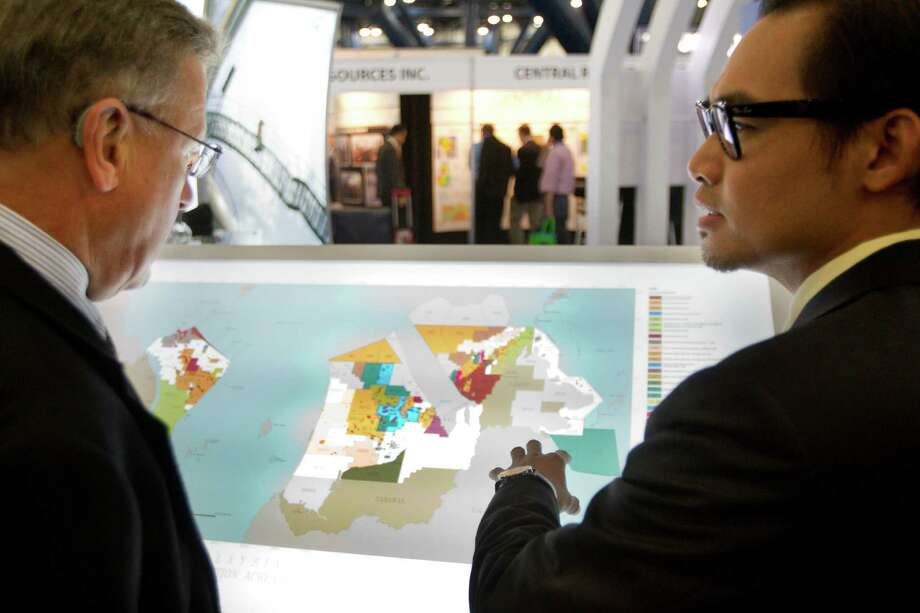 David Smith, of Newfield Exploration Company, left, looks at a map of exploration and production in Malaysia with Ahmad Januri, of Petronas, during the NAPE Expo at the George R. Brown Convention Center Tuesday, Feb. 5, 2013, in Houston. Photo: Brett Coomer, Houston Chronicle / © 2013 Houston Chronicle