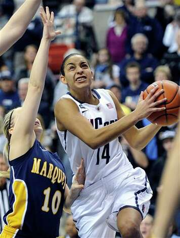 UConn's Bria Hartley, right, drives past Marquette's Brooklyn Pumroy during the first half of an NCAA college basketball game in Storrs, Conn., Tuesday, Feb. 5, 2013. (AP Photo/Fred Beckham)