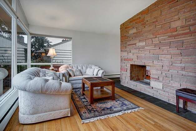 Living room of 6749 55th Ave. S. The 2,120-square-foot house, built in 1959, has four bedrooms, 2.75 bathrooms, vaulted ceilings, a two-way fireplace between the living room and dining room, a recreation room with a fireplace, a patio and a two-car garage on a 4,790-square-foot lot. It's listed for $515,000. Photo: Courtesy Liz Azose/Windermere Real Estate