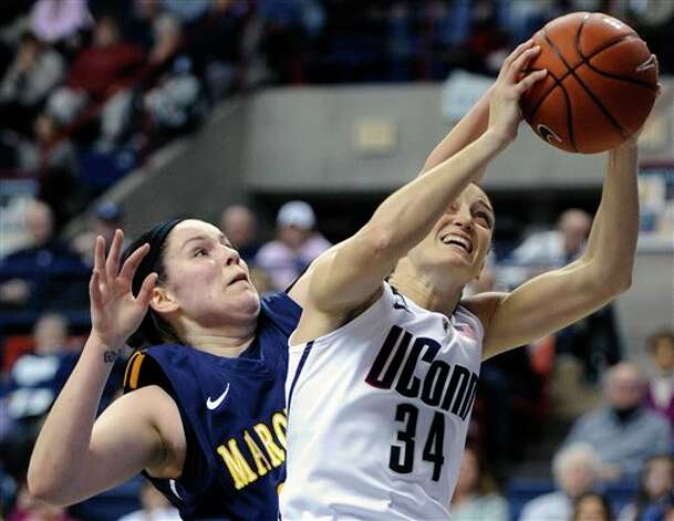 UConn's Kelly Faris, right, is pressured by Marquette's Cristina Bigca during the first half of an NCAA college basketball game in Storrs, Conn., Tuesday, Feb. 5, 2013. (AP Photo/Fred Beckham)