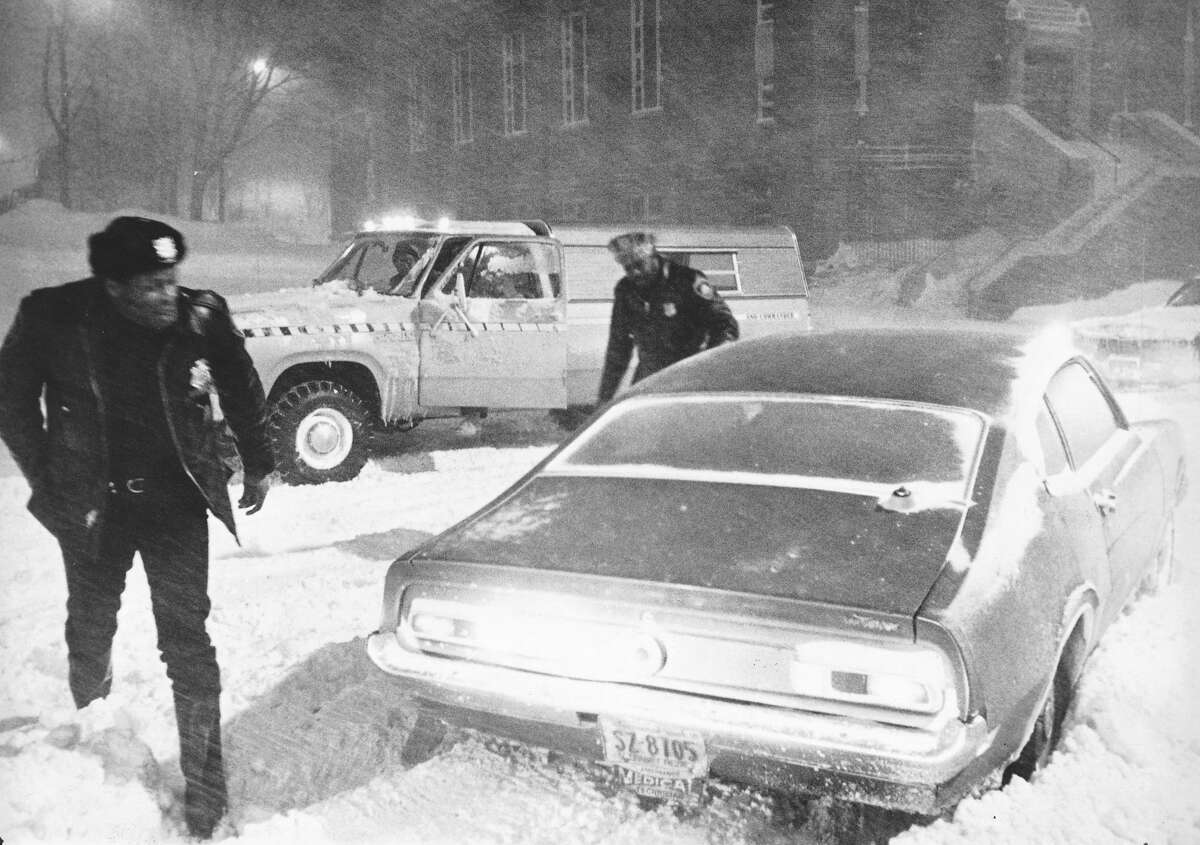 Feb. 7, 1978 - Two special police officers try to dig out a medical technician on the corner of Grove and Broad Streets in Stamford after the blizzard of 1978. The National Weather Service's latest estimate calls for 12 to 16 inches in southern Connecticut. The storm is being classified as a nor'easter, which simply means it's a storm along the east coast. The major difference between a blizzard and a regular snow storm is the strength of the wind, according to the National Weather Service. People tend to use the word