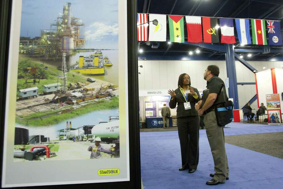 Sharon Kuhn, exploration geologist for Staatsolie, talks about oil lease blocks in Suriname with Sean Lewis of ExxonMobile during the NAPE expo in Houston. Photo: Brett Coomer / Houston Chronicle