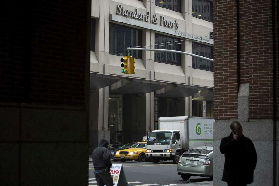Two pedestrians pass by Standard & Poor's New York City headquarters. The U.S. government is suing to recover as much as $5 billion from S&P for what it considers inflated credit ratings. Photo: Scott Eells / Bloomberg