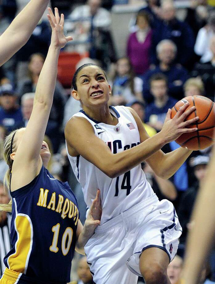 Connecticut's Bria Hartley, right, drives past Marquette's Brooklyn Pumroy during the first half of an NCAA college basketball game in Storrs, Conn., Tuesday, Feb. 5, 2013. (AP Photo/Fred Beckham) Photo: Fred Beckham, Associated Press / FR153656 AP