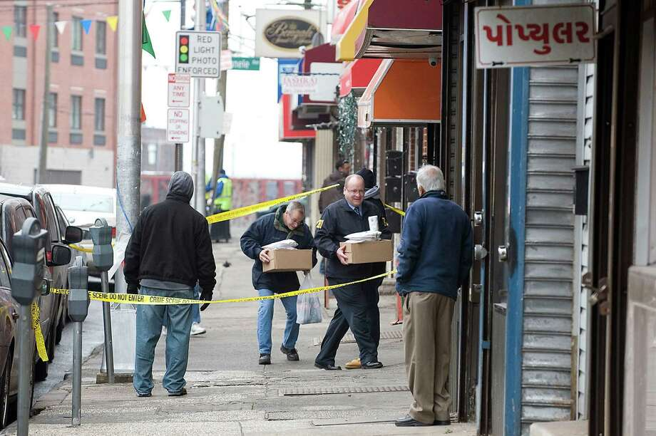 FBI agents enter Raja Jewelers at 820 Newark Ave. in Jersey City on Tuesday, Feb. 5, 2013, investigating an international credit card fraud ring. Eighteen people were charged in what may be one of the nation's largest credit card fraud rings, a sprawling international scam that duped credit-rating agencies and used thousands of fake identities to steal at least $200 million, federal authorities said Tuesday. (AP Photo/The Jersey Journal, Reena Rose Sibayan) Photo: REENA ROSE SIBAYAN
