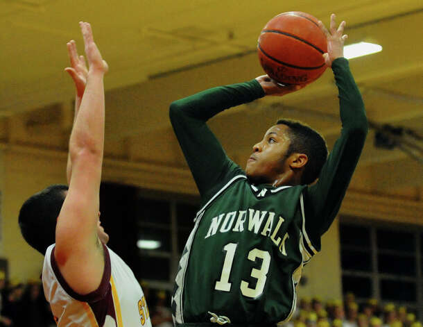 Norwalk's #13 Jeremy Linton attempts a shot, during boys basketball action against St. Joseph in Trumbull, Conn. on Tuesday February 2, 2013. Defening the net is St. Joseph's #5 Jonathan Dzurenda. Photo: Christian Abraham / Connecticut Post