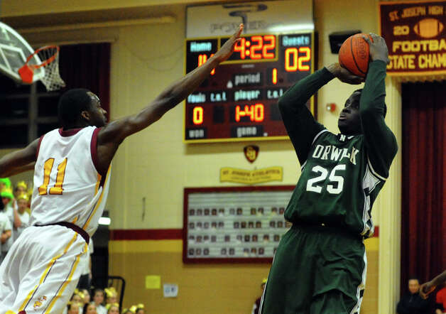 Norwalk's #25 Saeed Soulemane attempts a shot as St. Joseph's #11 Quincy McKnight reaches in to block, during boys basketball action in Trumbull, Conn. on Tuesday February 2, 2013. Photo: Christian Abraham / Connecticut Post