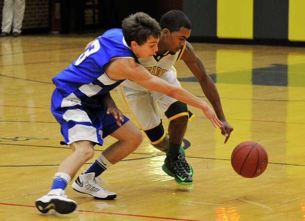 Fairfield Ludlowe's Danny Santella attempts to steal the ball from Trinity Catholic's Neno Merritt during their game at Trinity Catholic High School in Stamford on Tuesday, Feb. 5, 2013. Trinity Catholic beat Fairfield Ludlowe, 53-47. Photo: Jason Rearick / The News-Times