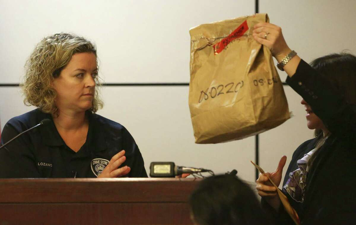 Police Department crime scene investigator Tiffany Lozano looks at an evidence bag held up by prosecutor Ana Liz De Leon-Vargas as the trial gets under way.