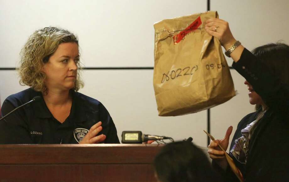 Police Department crime scene investigator Tiffany Lozano looks at an evidence bag held up by prosecutor Ana Liz De Leon-Vargas as the trial gets under way. Photo: Photos By William Luther / San Antonio Express-News