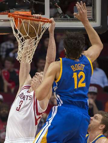 Houston Rockets' Omer Asik (3) dunks as Golden State Warriors' Andrew Bogut (12) defends during the first quarter of an NBA basketball game, Tuesday, Feb. 5, 2013, in Houston. (AP Photo/Dave Einsel) Photo: Dave Einsel, Associated Press