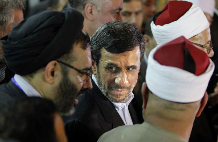 Iran's President Mahmoud Ahmadinejad (center) attends a news conference with Egyptian Sunni clerics as part of a landmark visit to Cairo, the first by an Iranian leader in decades. Photo: Amr Nabil / Associated Press