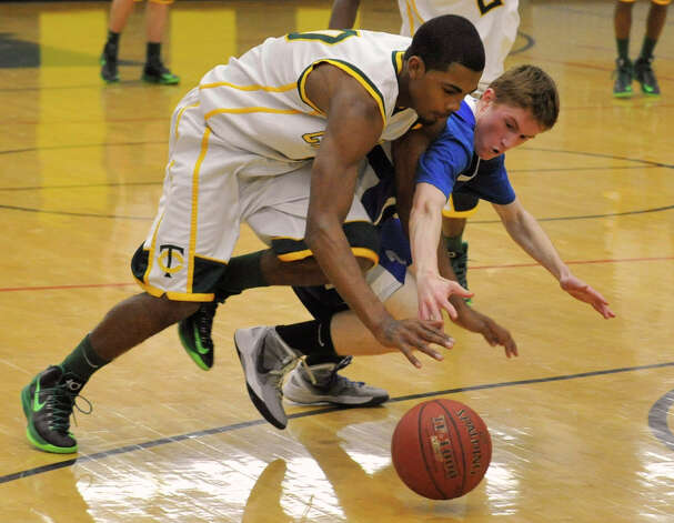 Trinity Catholic's Neno Merritt steals the ball from Mark Malone, of Fairfield Ludlowe, during their game at Trinity Catholic High School in Stamford on Tuesday, Feb. 5, 2013. Trinity Catholic beat Fairfield Ludlowe, 53-47. Photo: Jason Rearick / The News-Times