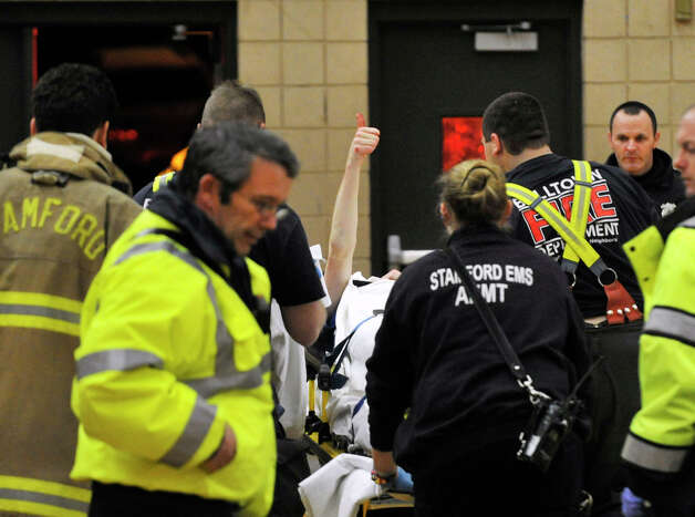 Fairfield Ludlowe's Mark Malone gives a thumbs up to a standing ovation as he is taken away by paramedics after injuring his head during Ludlowe's game against Trinity Catholic at Trinity Catholic High School in Stamford on Tuesday, Feb. 5, 2013. Trinity Catholic beat Fairfield Ludlowe, 53-47. Photo: Jason Rearick / The News-Times