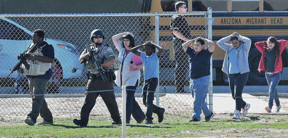 Students from an elementary school in Yuma, Ariz., are evacuated by armed police officers Tuesday after three schools went into lockdown when police responded to a call of a student possibly armed with a gun at an elementary school. Students were taken to another school several miles away. Police said they didn't find a weapon. Photo: Craig Fry / Yuma Sun