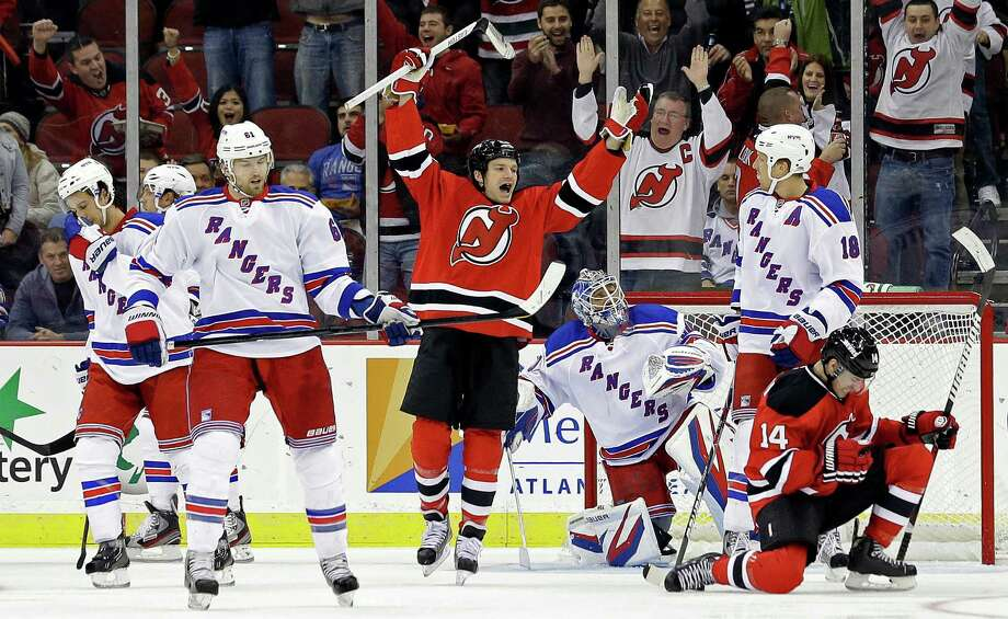 New Jersey Devils' Adam Henrique (14) celebrates with teammate David Clarkson, center right, after scoring a goal against the New York Rangers during the first period of an NHL hockey game, Tuesday, Feb. 5, 2013, in Newark, N.J. (AP Photo/Julio Cortez) Photo: Julio Cortez