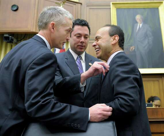 House Judiciary Committee member Rep. Jason Chaffetz, R-Utah, center, adjusts the flag pin on fellow committee member Rep. Luis Gutierrez, D-Ill., right, as they share a laugh with Rep. Trey Gowdy, R-S.C., on Capitol Hill in Washington, Tuesday, Feb. 5, 2013, prior to the committee's hearing on America's Immigration System: Opportunities for Legal Immigration and Enforcement of Laws against Illegal Immigration.  (AP Photo/Susan Walsh) Photo: Susan Walsh