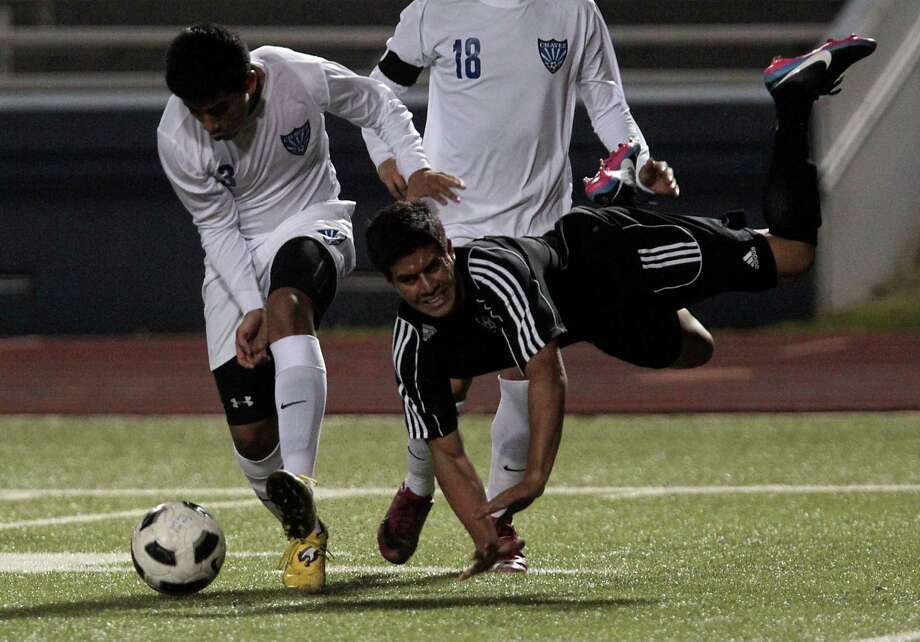 Chavez' Maynor Hernandez left, and teammate Angel Garcia right, chase the ball as Westside's Jonathan Garay center falls to the ground during the first half of boys high school soccer game action at HISD's Barnett Stadium Tuesday, Feb. 5, 2013, in Houston. Photo: James Nielsen, Chronicle / © Houston Chronicle 2013