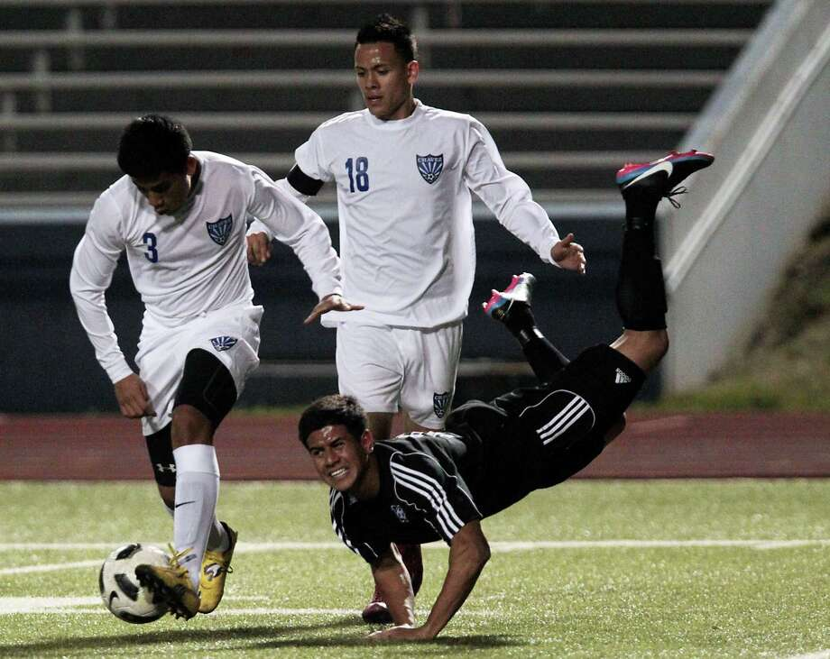 Chavez' Maynor Hernandez left, and teammate Angel Garcia right, chase the ball as Westside's Jonathan Garay center falls to the ground. Photo: James Nielsen, Chronicle / © Houston Chronicle 2013